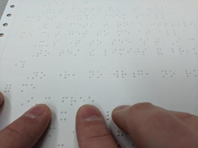 A hand reading Braille on a sheet.